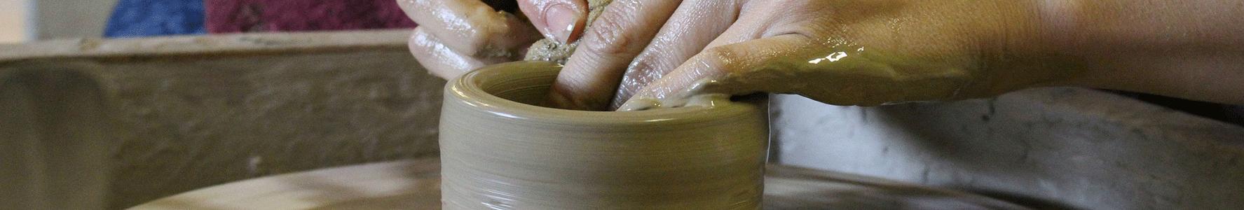 mani di donna al torno ceramica e argilla